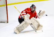 Hockey goalie in generic red equipment protects gate