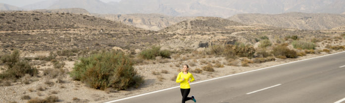 young attractive sport woman running on asphalt road with desert mountain landscape background looking happy and healthy in jogging training workout , fitness and wellness concept